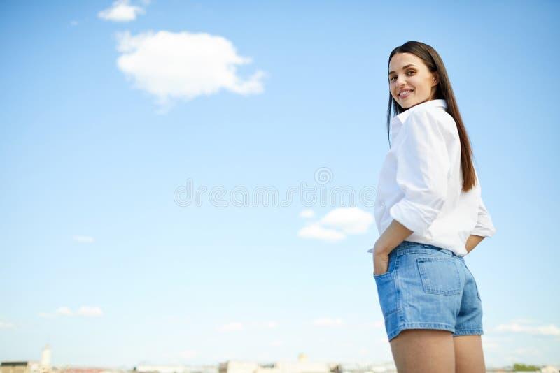 Fille moderne de sourire contre le ciel photographie stock libre de droits