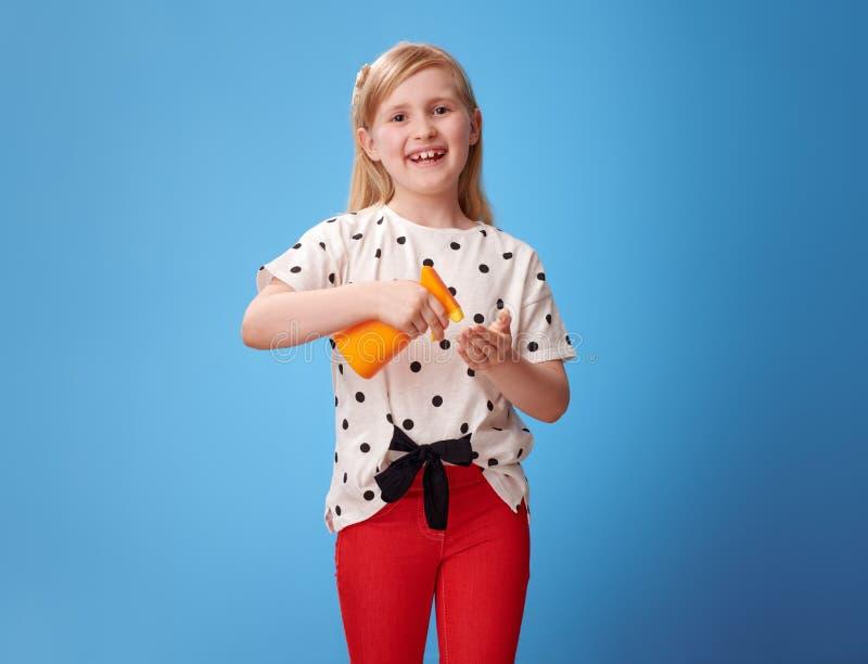 Fille moderne de sourire dans le pantalon rouge sur l'écran de soleil de application bleu image stock