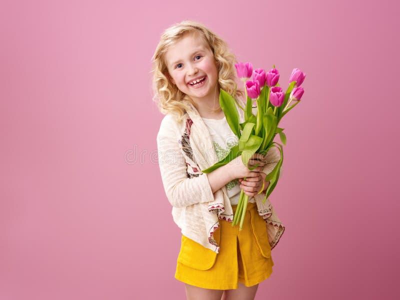 Fille moderne de sourire sur le fond rose avec le bouquet des fleurs photographie stock libre de droits