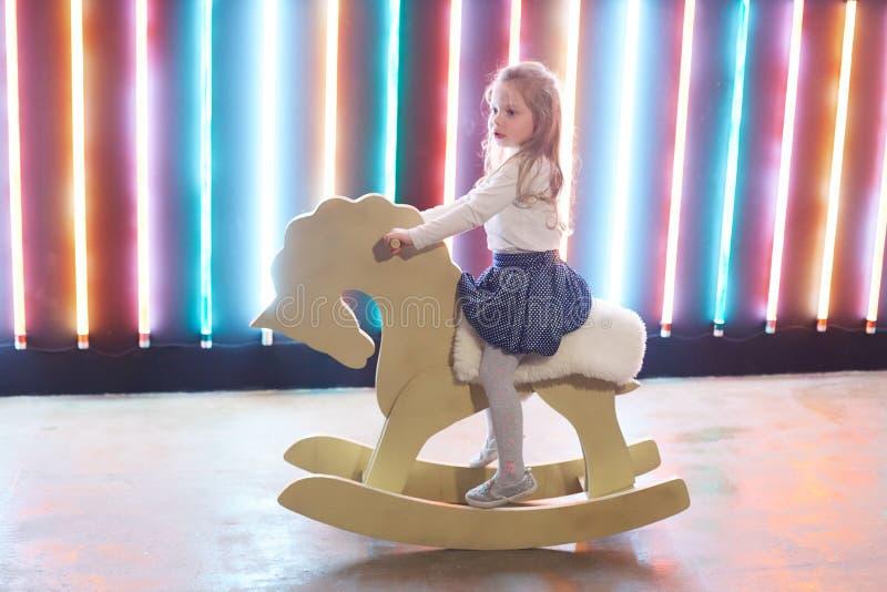 Fille montant un cheval basculant dans un studio peu commun de grenier photos libres de droits