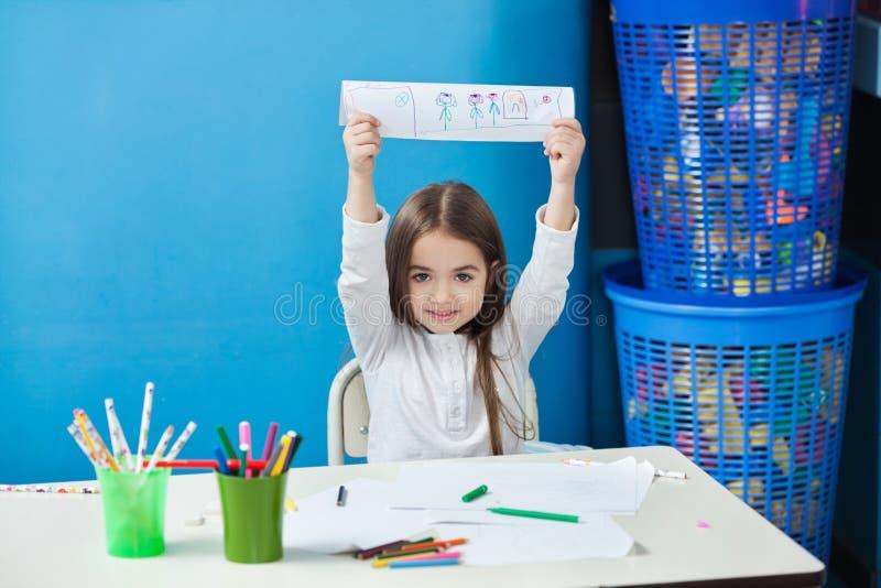 Fille montrant le dessin dans la salle de classe photo stock