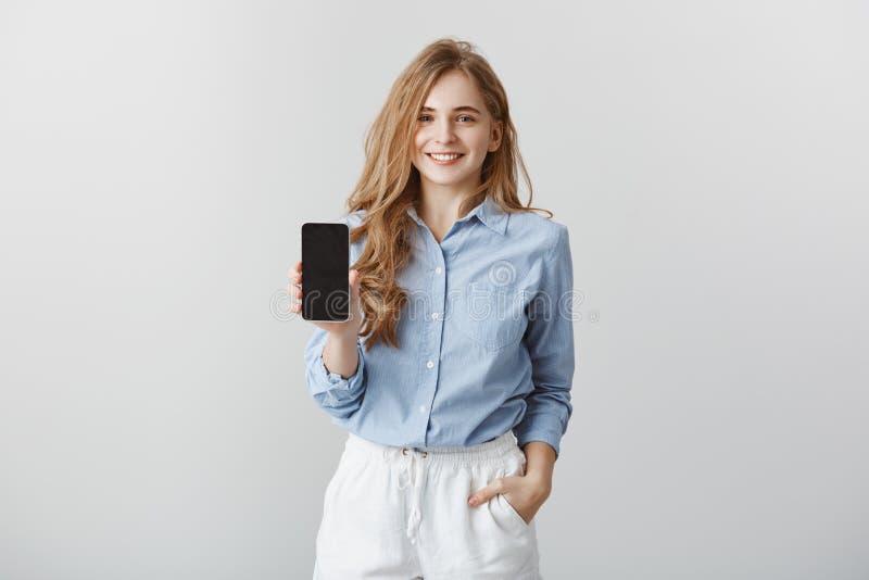 Fille montrant le nouveau téléphone au collègue Portrait de blogger européen à l'air amical avec du charme de mode dans le bleu f photo libre de droits