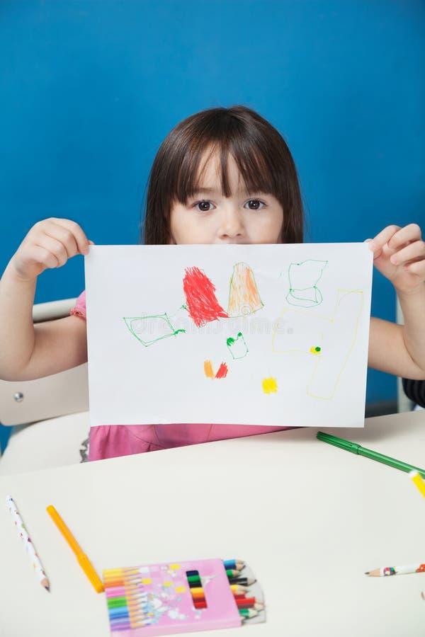 Fille montrant le papier de dessin dans la salle de classe photographie stock libre de droits