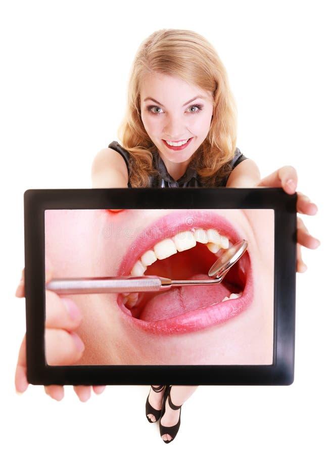 Fille montrant le touchpad de comprimé d'ipad avec la photo dentaire des dents photographie stock libre de droits