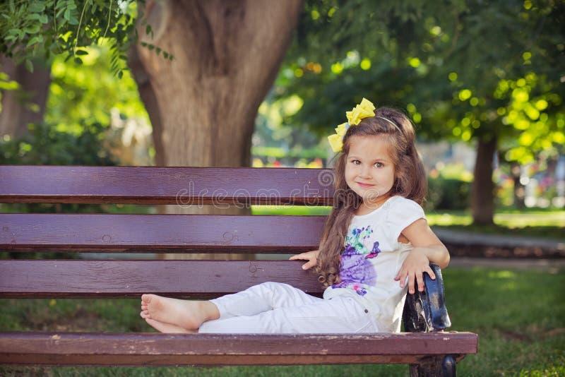 Fille musicale mignonne d'enfant de bébé avec des poils de brune et l'usage élégant appréciant la vie se reposant sur le banc en  photos libres de droits