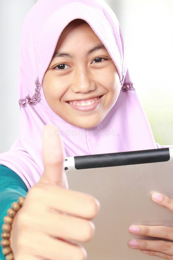 Fille musulmane à l'aide de la tablette photographie stock libre de droits