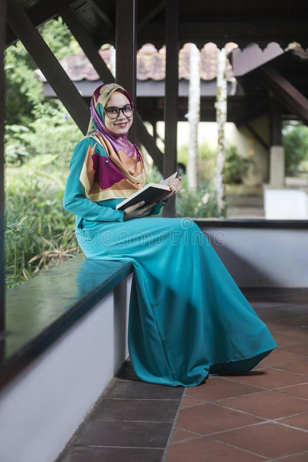 Fille musulmane tenant le livre au parc photographie stock