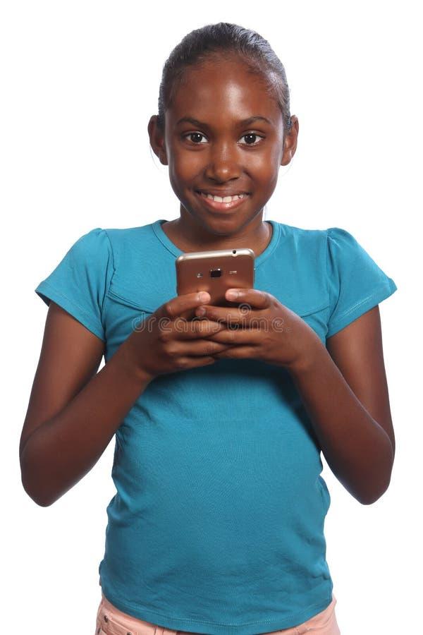 Fille noire de sourire d'école tenant son téléphone portable photographie stock
