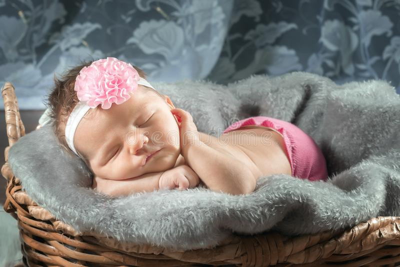 Fille nouveau-née de sommeil avec un arc rose images stock