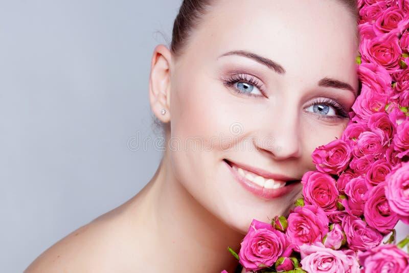 Fille observée d'une chevelure et bleue assez blonde avec des roses images stock