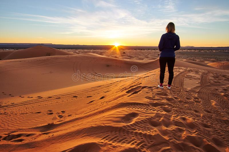 Fille observant le lever de soleil sur la dune de sable dans le désert du Sahara image stock