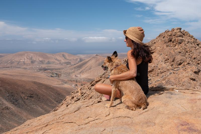 Fille observant le panorama avec son chiot photo stock