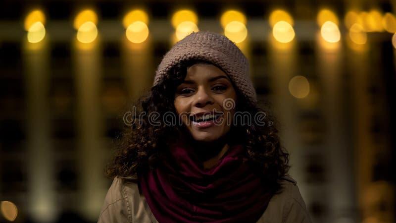 Fille occasionnelle aux cheveux bouclés mignonne posant et souriant sincèrement à l'appareil-photo, dame heureuse image libre de droits