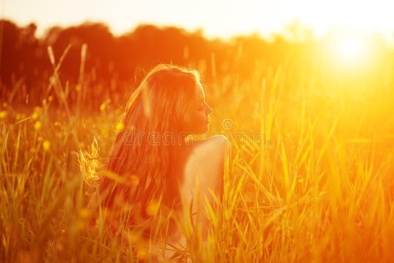 Fille occasionnelle de jeune de hippie femme de modèle dans le domaine dans le coucher du soleil dans le spri image libre de droits