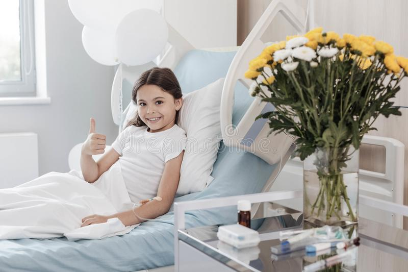 Fille occupée positive maniant maladroitement tout en se situant dans le lit d'hôpital photographie stock