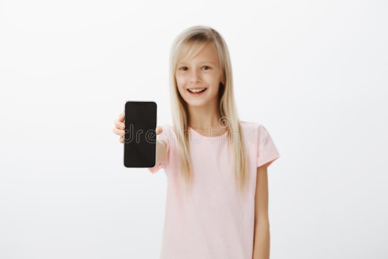 Fille optimiste montrant le nouveau téléphone portable aux amis Enfant mignon heureux avec les cheveux blonds, tirant la main ave images stock