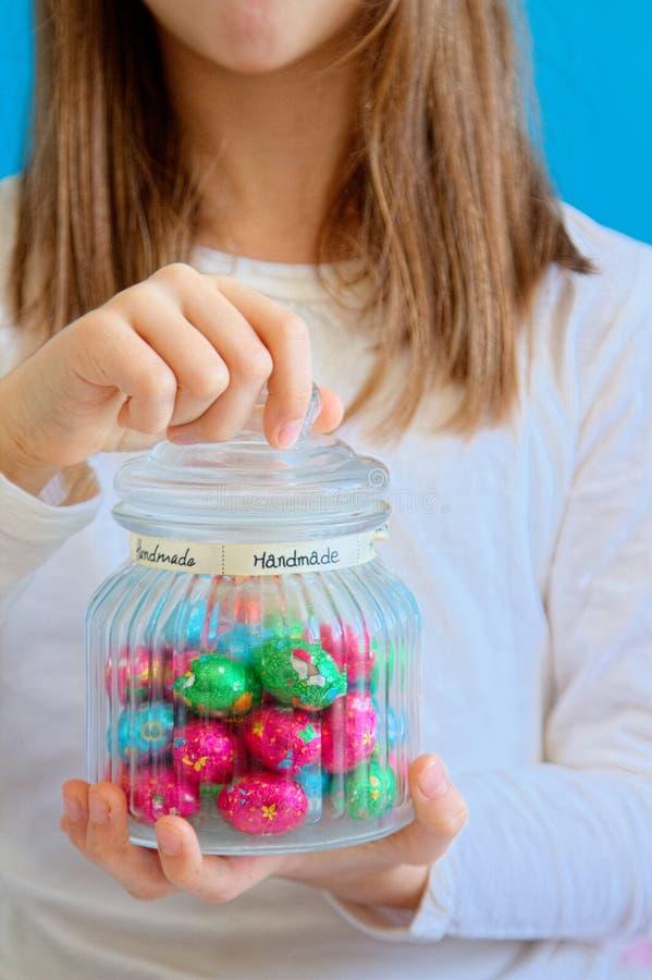 Fille ouvrant un pot de sucrerie sous emballage souple colorée d'oeufs de chocolat photos libres de droits