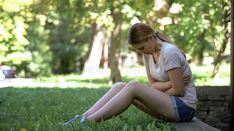 Fille pâle souffrant la douleur abdominale dehors, le mal ou l'indigestion menstruel image stock