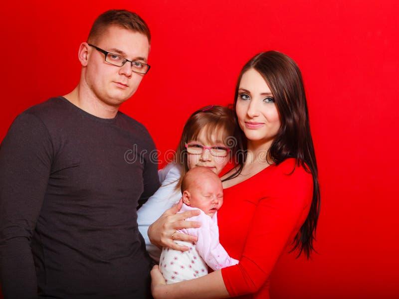 Fille, père et mère d'enfant en bas âge tenant le bébé nouveau-né image stock