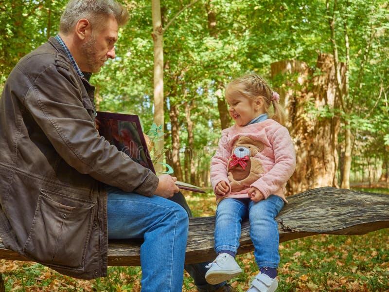 Fille, père, jeune, livre, maison, enfant, papa, beau, s'asseyant, mâle, parenting de famille, mignon, lisant, peu, ensemble, peo photographie stock libre de droits