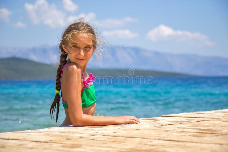Fille par la jetée en bois en mer photographie stock
