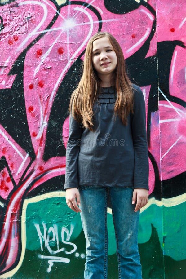 Fille par un mur de graffiti images stock