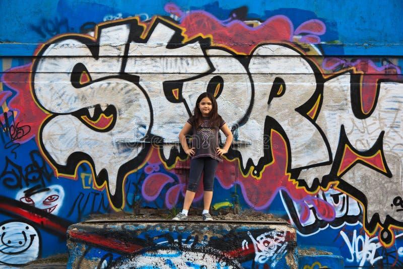 Fille par un mur de graffiti photographie stock