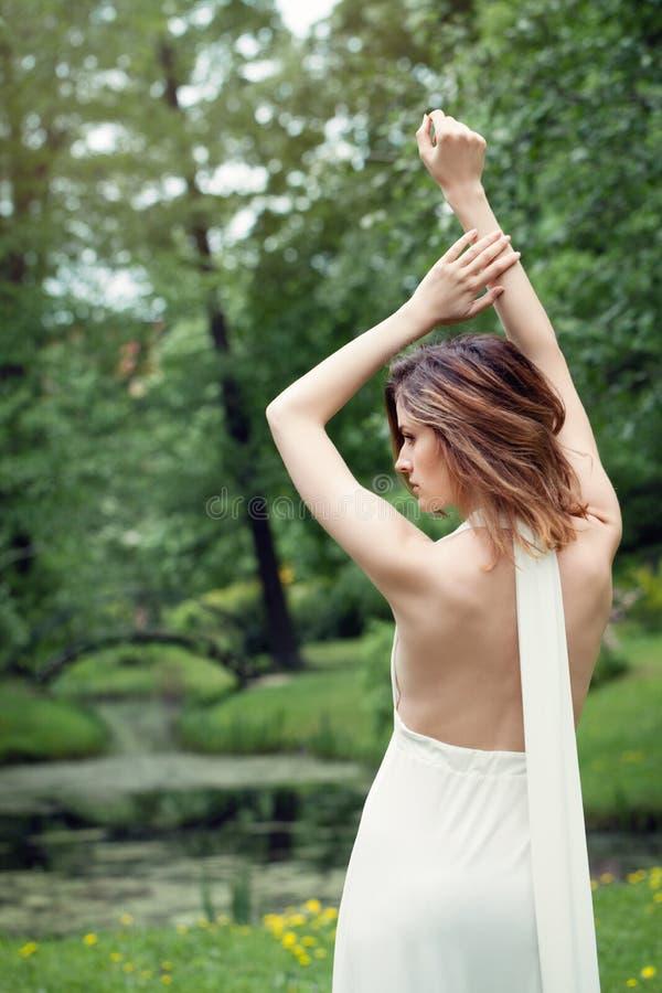 Fille parfaite dans la robe blanche extérieure Beau dos femelle sur le fond vert de nature photographie stock