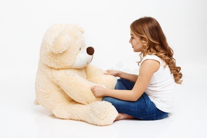 Fille parlant à l'ours de jouet car c'est un ami image stock