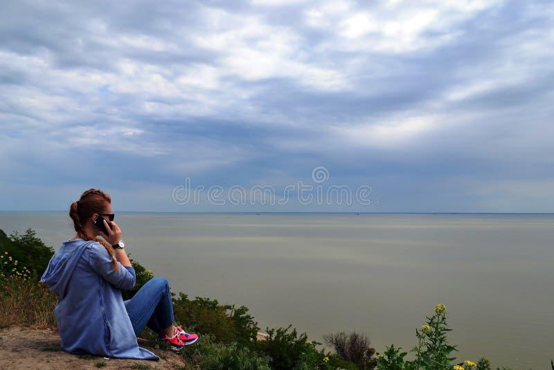 Fille parlant au téléphone sur la plage et regardant la mer photos stock