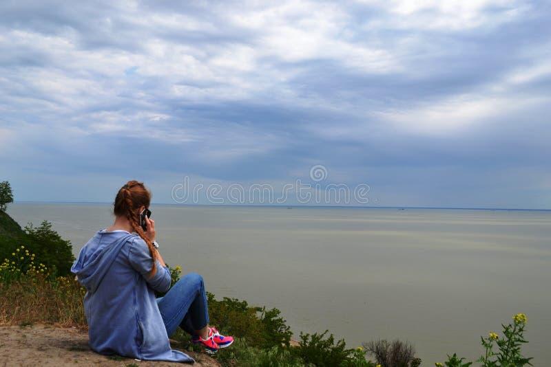 Fille parlant au t?l?phone sur la plage et regardant la mer photos libres de droits