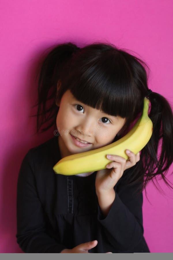 Fille parlant sur une banane photos stock