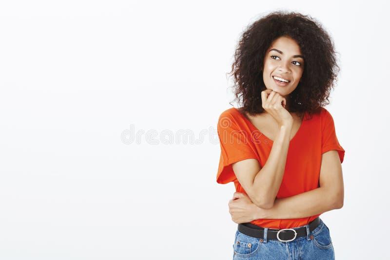 Fille pensant ou ayant l'idée intéressante Femme à la peau foncée avec du charme intriguée avec la coiffure Afro, tenant la main  images libres de droits