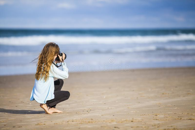 Fille photographiant la mer photo stock