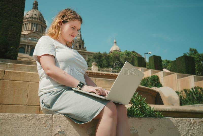 Fille plus de modèle de taille travaillant sur l'ordinateur portable dehors image stock