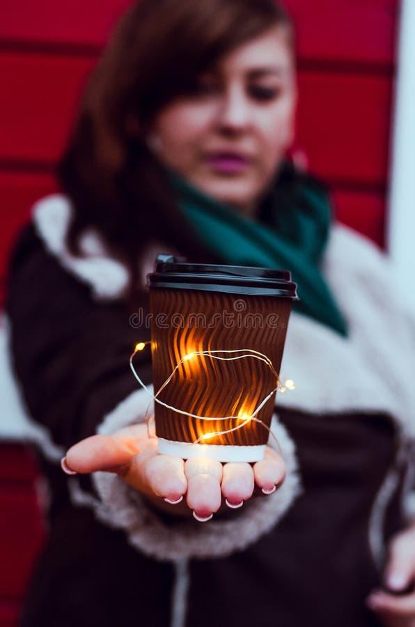 Fille plus la taille avec un verre de café et d'une guirlande lumineuse photos libres de droits
