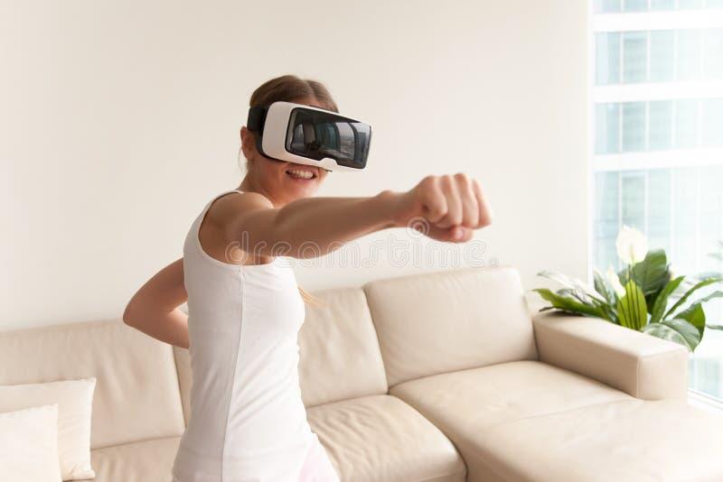 Fille portant des lunettes de VR jouant le jeu, enfermant dans une boîte dans la réalité virtuelle photos libres de droits