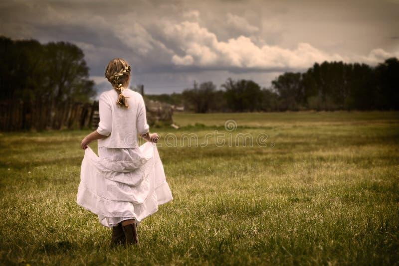 Fille portant une robe marchant dans un pâturage image libre de droits