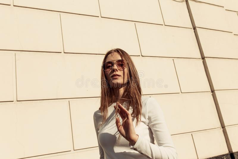 Fille posant contre un mur de briques blanc image libre de droits