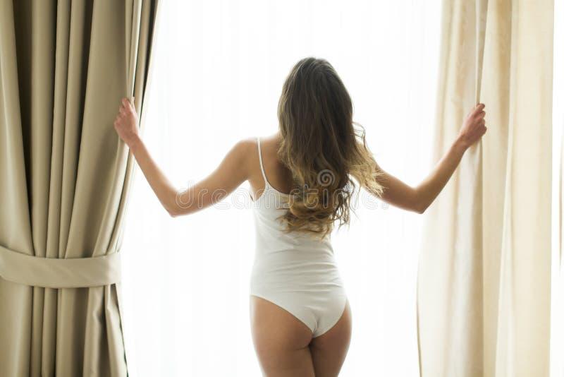 Fille posant dans les sous-vêtements par la fenêtre photographie stock libre de droits