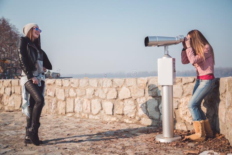 Fille posant devant le télescope de jumelles photo stock