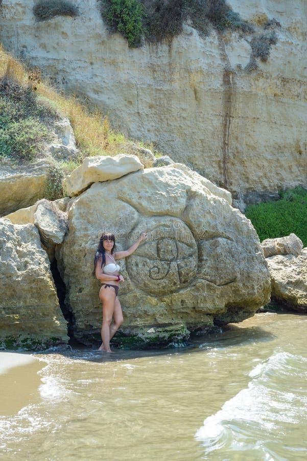 Fille posant près de la roche photographie stock