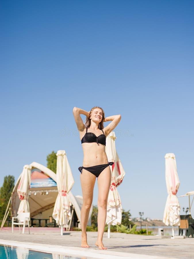 Fille positive et jolie dans un bikini marchant sur un fond de piscine Concept de station de vacances Copiez l'espace photographie stock