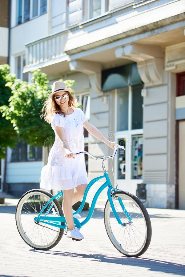 Fille positive souriant à l'appareil-photo tout en montant le vélo bleu au centre de la ville avec de beaux bâtiments et arbres v photo libre de droits