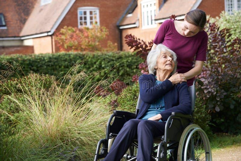 Fille poussant la mère supérieure dans le fauteuil roulant photographie stock
