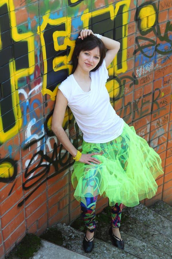 Fille près du mur avec le graffiti photographie stock libre de droits