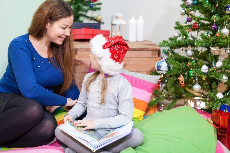 Fille préscolaire avec la mère s'asseyant sur le plancher à côté de l'arbre de Noël images libres de droits