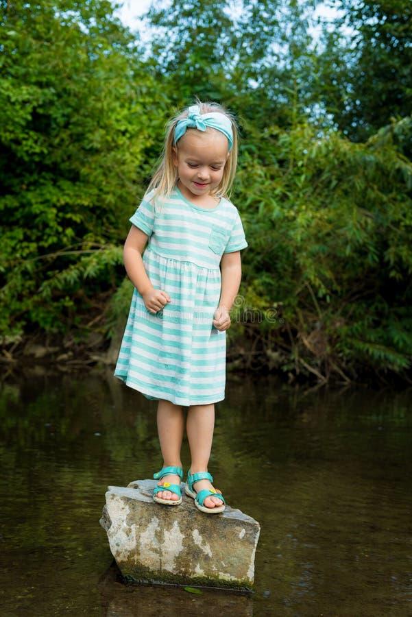 Fille préscolaire blonde adorable jouant en rivière image libre de droits