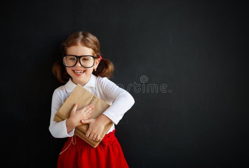 Fille préscolaire d'écolière heureuse avec le livre près du tableau noir d'école photo libre de droits
