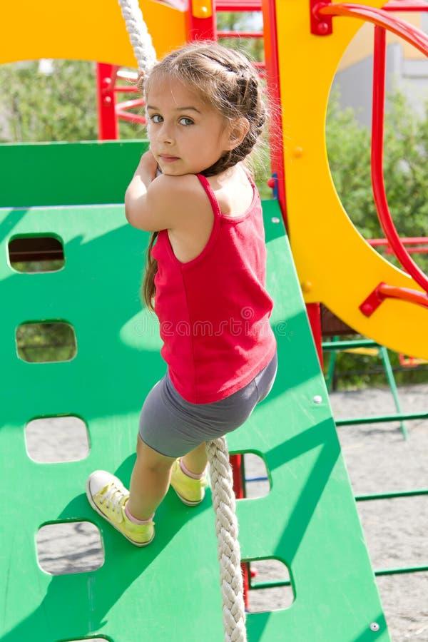 Fille préscolaire jouant sur le terrain de jeu, escaladant le mur sur une corde images libres de droits